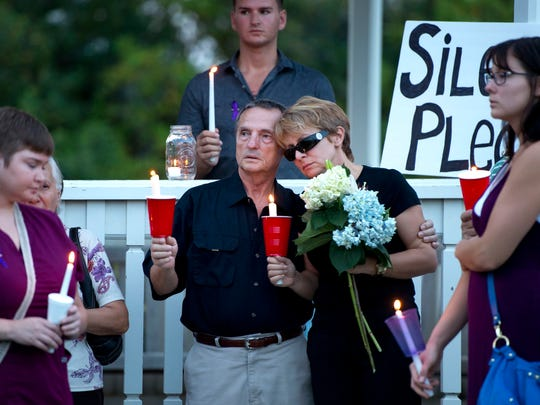 Bill and Lena Andrews (center) stand with candles and flowers while attending a candlelight vigil at Riverside Park. The Andrews' daughter, Diana Duve, was killed in 2017. Duve's former boyfriend, Michael Jones, was convicted of her murder this week.