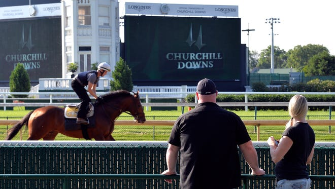 Rebecca Pauley, right, and Todd Deming of French Creek, West Virginia watch as horses work out at Churchill Downs, Saturday, May 30, 2015. (Timothy D. Easley/Special to the C-J)