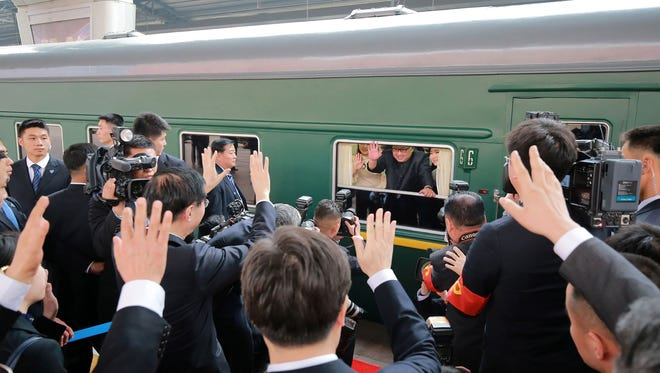 North Korean leader Kim Jong Un  waves from his train as it prepares to depart from Beijing railway station.