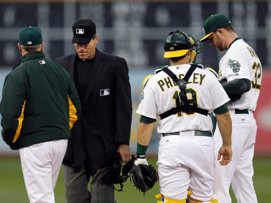 Oakland Athletics pitcher Jesse Hahn, right, is visited by, from left to right, pitching coach Curt Young, home plate umpire Angel Hernandez and catcher Josh Phegley in the first inning of a baseball game against the Chicago White Sox, Friday, May 15, 2015, in Oakland, Calif. (AP Photo/Ben Margot)