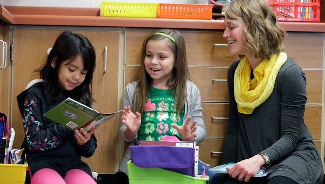 First-grade students Stephanie Lopez Rivera (left) and Isabel Erdman participate in partner reading with the guidance of their teacher Emily Thomas on Monday at Horizons Elementary School in Appleton. Horizons is part of a state program to reduce class sizes.
