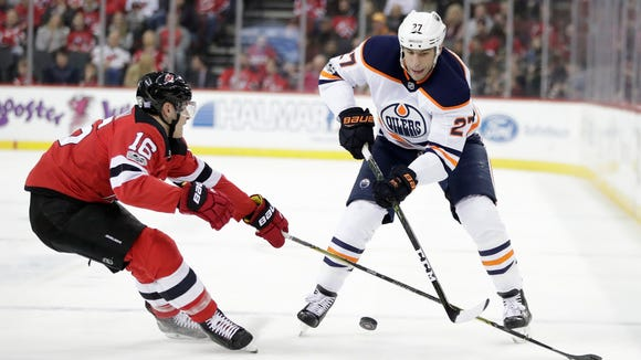 New Jersey Devils defenseman Steven Santini (16) defends Edmonton Oilers left wing Milan Lucic (27) during the first period of an NHL hockey game, Thursday, Nov. 9, 2017, in Newark, N.J. (AP Photo/Julio Cortez)
