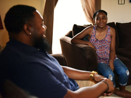 Diovian Williams, 13, right, talks with her father Roderick Williams at their home in Jackson Tuesday.