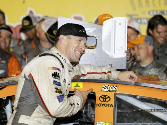 Carl Edwards points at his 2 checkered flag decals after winning a NASCAR Sprint Cup auto race at Darlington Raceway in Darlington, S.C., Sunday.