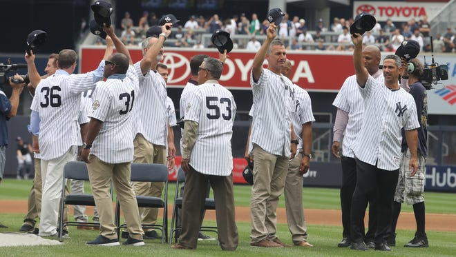 The players salute the fans as they give applaud the 1998 World Series champions.