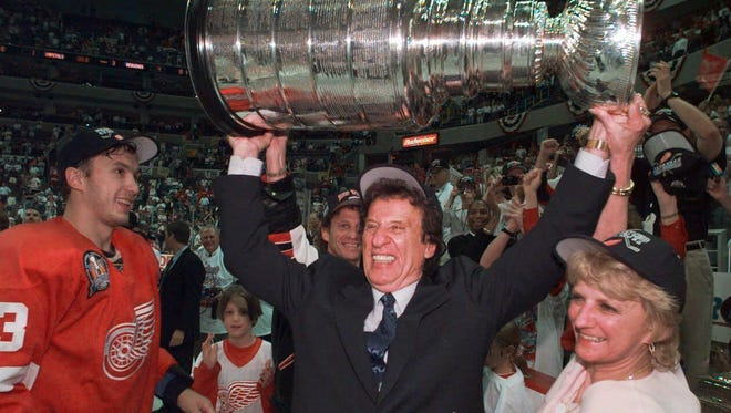 In this 1998 photo, Red Wings owner Mike Ilitch, center, hoists the Stanley Cup after the Red Wings won their second consecutive NHL championship.