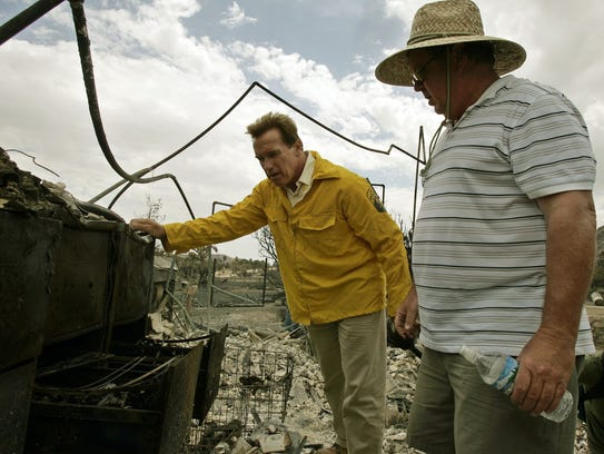 California Governor Arnold Schwarzenegger examines the remains of a home owned by Jim Brock, right, Monday, July 17, 2006, after touring the area damaged by the Sawtooth wildfire in Yucca Valley, Calif.