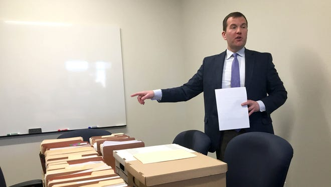 Andrew Brisbo, director of the state's Bureau of Medical Marijuana Regulation, with the filings associated with one business' application for a medical marijuana license on Tuesday, May 1, 2018 at the BMMR offices in Lansing.