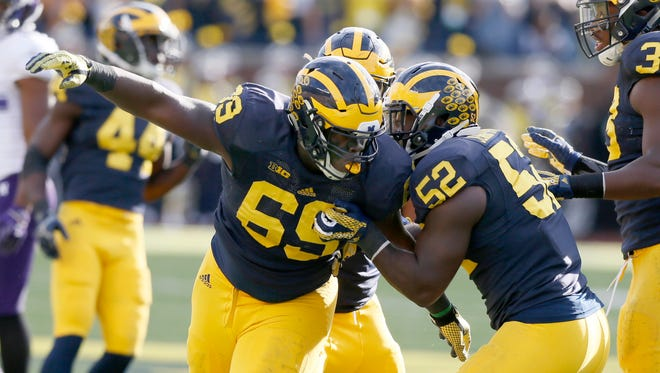 Michigan's Willie Henry, left, celebrates his sack with Royce Jenkins-Stone, right against Northwestern on Oct. 10, 2015.