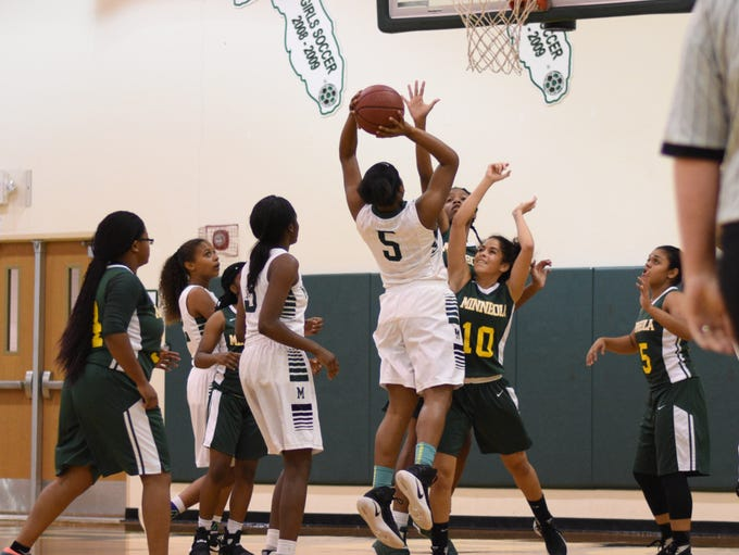 MHS's Alasia Spivey (5) shoots over the defense of
