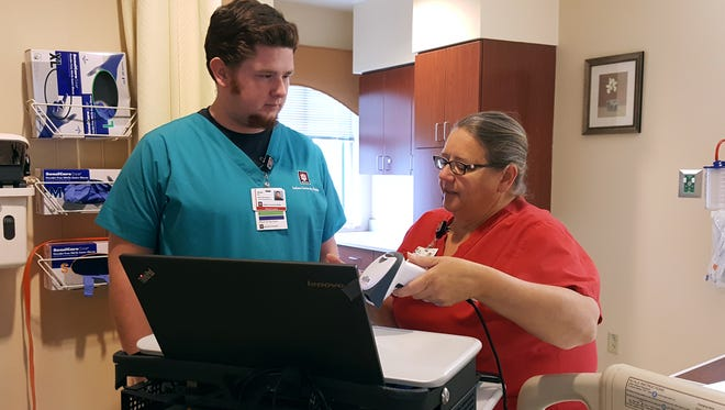 Blackford Hospital clinical staffers Trevor Hill, PCA, and Linda Morgan, RN, are shown scanning records in a manner that makes them secure, yet accessible to medical professionals (electronic medical records). IU Health Blackford Hospital has been named as one of the nation's Most Wired® Hospitals.