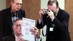 Volusia County canvassing board chairman, Judge Michael McDermott, holds up an invalid ballot as Bush lawyer Lawrence J. Halloran takes a photo of it during the recount of the 2000 Bush v. Gore presidential election.