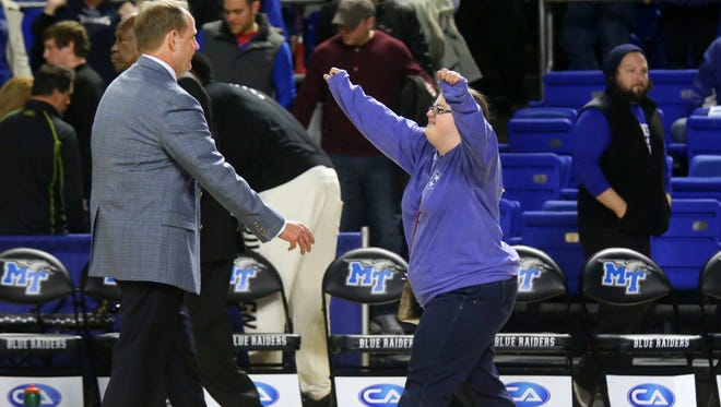 Ally Davis, right, walks up to her dad, MTSU men's basketball Coach Kermit Davis, left, to give him a hug after MTSU men beat North Texas 86-64, on Thursday, Jan. 21, 2016, at MTSU.