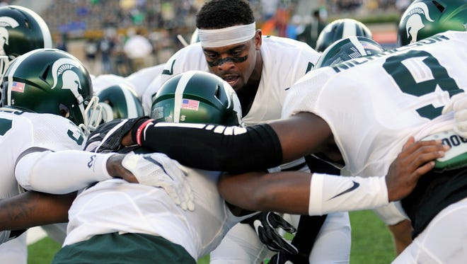 MSU senior safety Demetrious Cox senior (center, facing), gets the rest of the Spartans' defensive backfield, including his partner at safety Montae Nicholson (9), pumped up before MSU's game at Notre Dame on Sept. 17.