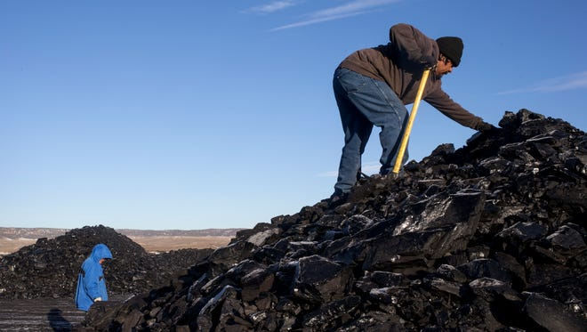 Darryl Sahmea (right) searches for quality pieces of coal at the Kayenta Mine in Black Mesa, Ariz., on Feb. 4, 2017. Many Hopi and Navjo tribe members rely on the free coal to heat their homes with coal stoves in the winter months.