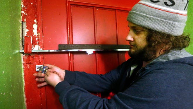 """Marshall Pointer, an employee of Enchanted Planet removes the padlock from the back door of the store after Judge Royce Taylor allowed stores that were padlocked by authorities to be reopened after they were closed following the """"Operation Candy Crush"""" CBD raids earlier this month, following the arraignments on Friday Feb. 16, 2018."""
