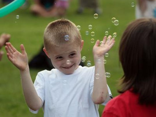 Phillip Hebbe, 7, of Wausau, bats at bubbles blown by Casey Romansik, 8, of Wausau, right, during Wausau's Summer Kickoff Celebration at Oak Island Park in 2013.