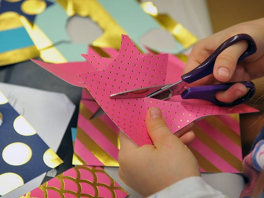 Mercie Abila, 8, cuts out a star shape for her rocket