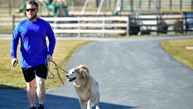 Nate Sourbier walked his dog, Parker, along the path at Norlo Park on a balmy Monday, Feb. 6, 2017, that saw temperatures reach into the high 50s.