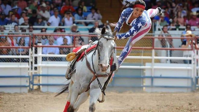 A Riata Ranch Cowboy Girl performs trick riding maneuvers.