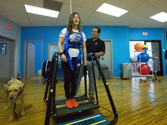Letticia Martinez, center, works on her balance with the help of David Gallegos, an athletic trainer at Southwest Sport and Spine Center, during a therapy session.