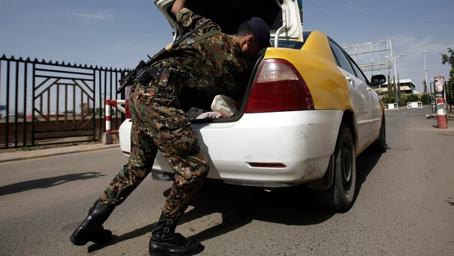 A policeman checks a car at the entrance of Sanaa International Airport in Yemen on Aug. 7. Yemen is on high alert for terror threats