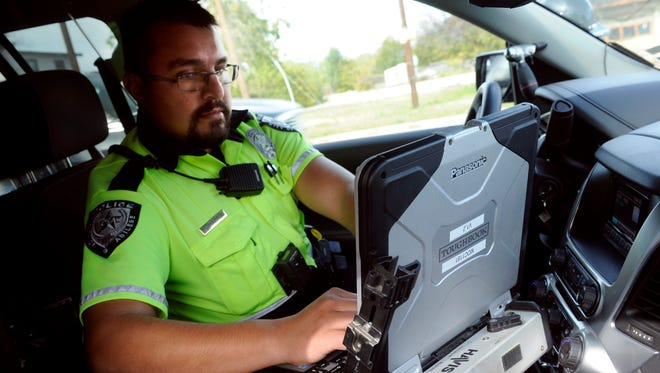 Abilene Police Department traffic officer Michael Garcia uses the computer in his patrol vehicle to research the driving record of a motorist he pulled over Nov. 18.