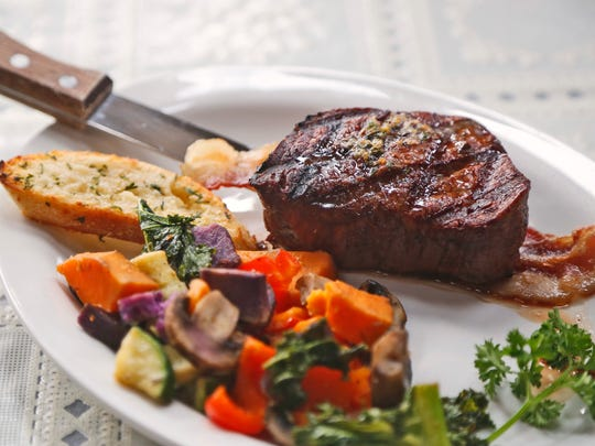 A hand-cut 8-ounce filet mignon with herb butter from