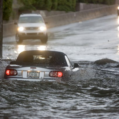 Floodwater nearly engulfs a car on McClintock Drive