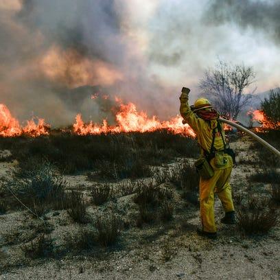 A firefighter battles the Esperanza Fire near Poppet