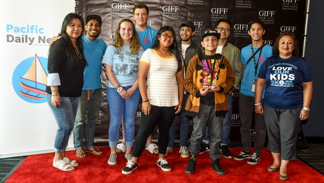 Rindraty Celes Limtiaco, left, Pacific Daily News publisher and president, is joined by Don Muña, second from left, Guam International Film Festival co-founder and executive director, Therese Arriola, far right, executive director of Sanctuary Inc. and the winners of the GIFF/PDN Island-wide Youth Film Competition winners, after a viewing was held of the winning film entries at the Guam Museum on Saturday, April 28, 2018.