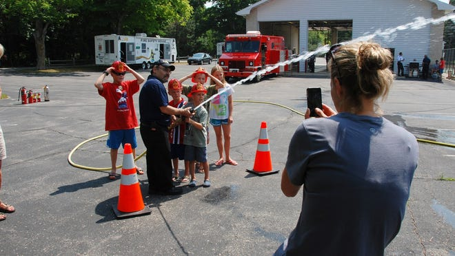 Kirsten Healey, vacationing from Boston, records her family as they have fun with firefighter Bob Volpe, during the hose demonstration for kids by the Ephraim Fire Department Saturday.