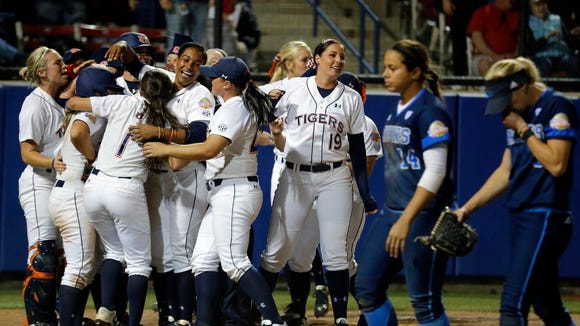 Auburn celebrates a walk-off walk as UCLA's Mysha Sataraka (14) and Ally Carda (3) walk of the field in the 10th inning during an NCAA Women's College World Series game in Oklahoma City, Saturday, May 30, 2015.