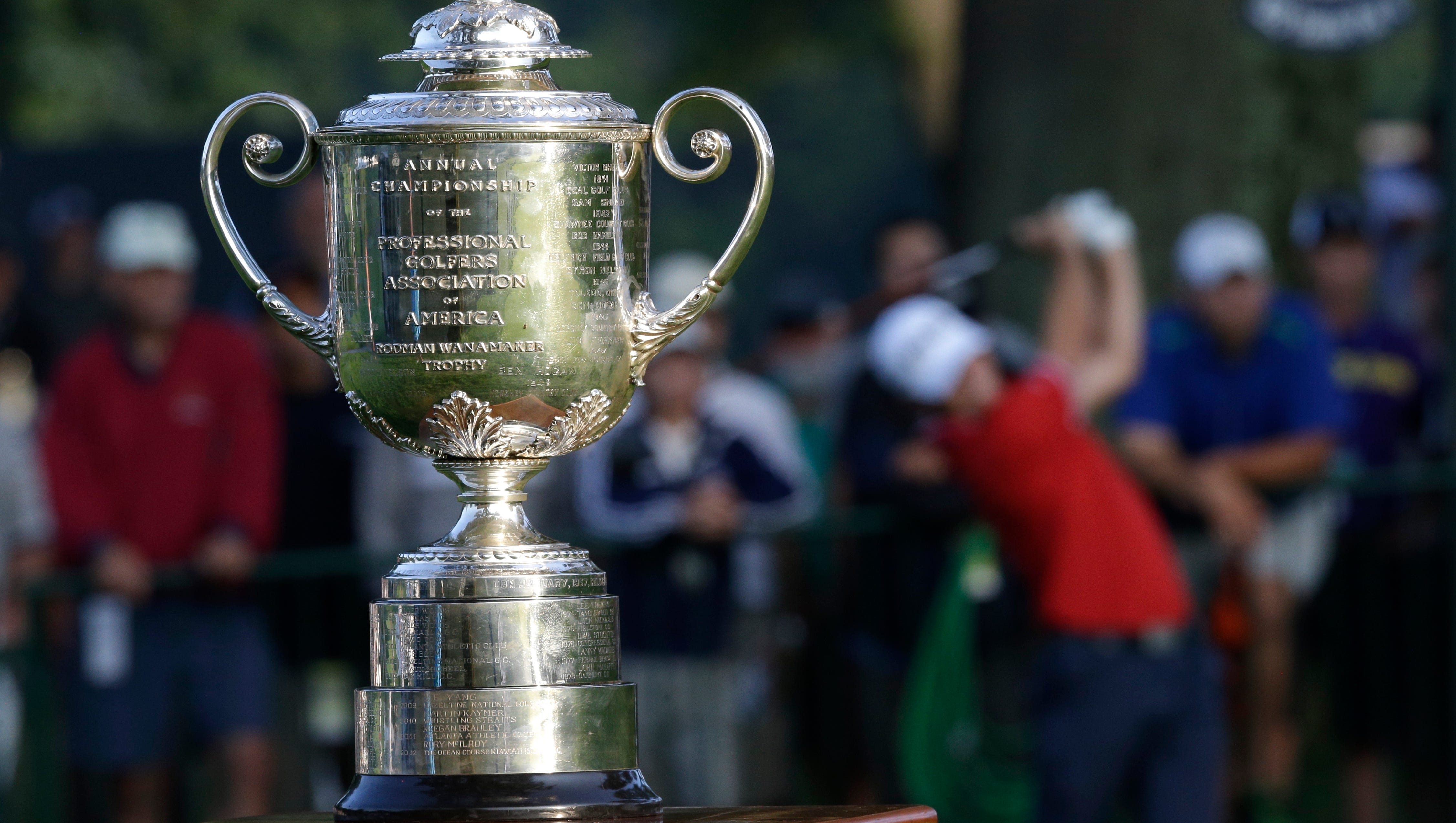 The Wanamaker Trophy is displayed near the first hole as Luke Guthrie tees off.