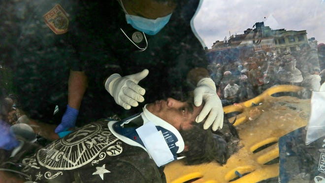 A U.S. doctor attends to Pemba Tamang inside an ambulance after Tamang was  rescued by Nepalese police and U.S. rescue workers from a building that collapsed five days ago.