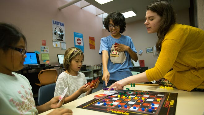 """Christian Martinez, center, (12) joins in the board game """"Cross Ways"""" at the Thomas Branigan Memorial Library on Tuesday June 28, 2016 during game night along with Alexis Orona, left, (10), Erica Padron (10), and Teen Librarian Stephanie Midwood."""