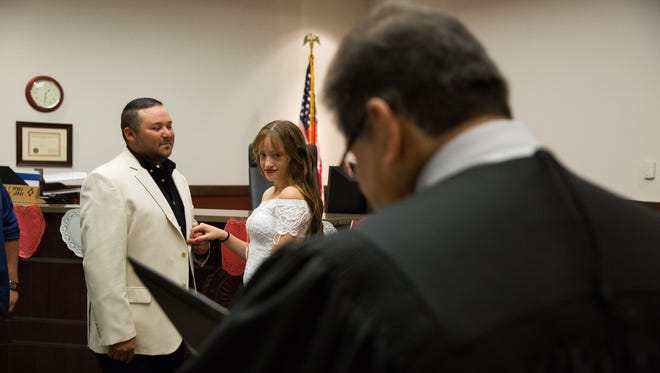 Robert Castillo and his fiancée Mariesol Martinez, hold hands as Doña Ana Magistrate Court Judge Conrad Perea at the Doña Ana County Magistrates Court, Tuesday, February 14, 2017. It has become tradition for a court to be set aside for couples that would like to be married on Valentine's Day,