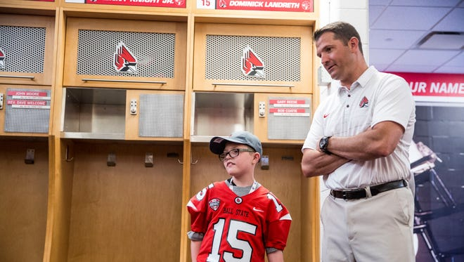 Ball State head coach Mike Neu talks with Dominick Landreth, 9, who signed an official letter of intent to join Ball State's football team. The program was part of national nonprofit Team IMPACT who help match up sports teams with chronically ill children.