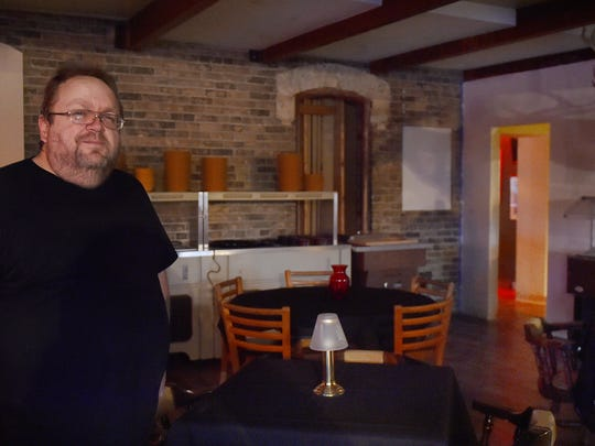 """While remodeling one of the dining rooms at the Alaskan Motor Inn, owner Sam Williquette uncovered the outside brick wall of the original farmhouse, background, housing the bar area. Additions throughout the years have extended the facility to include a supper club. Wiliquette hopes to open the dining rooms by Dec. 1 or """"sooner.'' The bar area has been open since October."""
