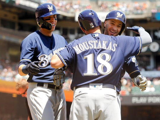 Brewers outfielder Ryan Braun (right) celebrates with Mike Moustakas (18) and Christian Yelich after Braun hit a two-run home run in the first inning for a 2-0 run lead.