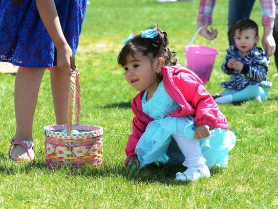 This girl picks up colored Easter eggs at the 2015