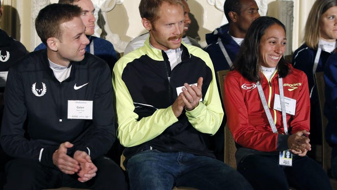 U.S. distance runners Galen Rupp (left) Jared Ward (center) and Desiree Linden applaud during a Boston Marathon media availability Friday, in advance of Monday's race in Boston.