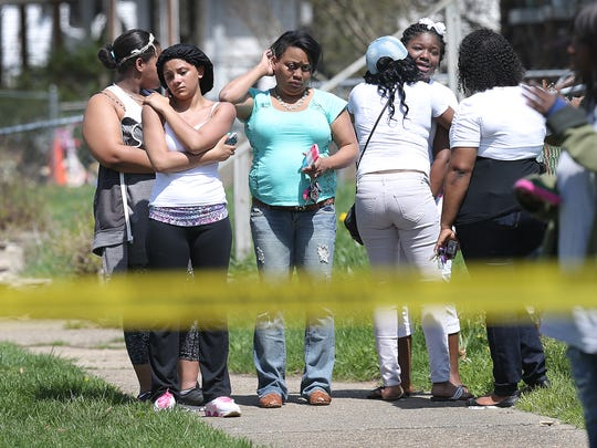 Neighbors gather near the scene of a fatal shooting at 1922 N. Adams St. Friday, April 17, 2015.