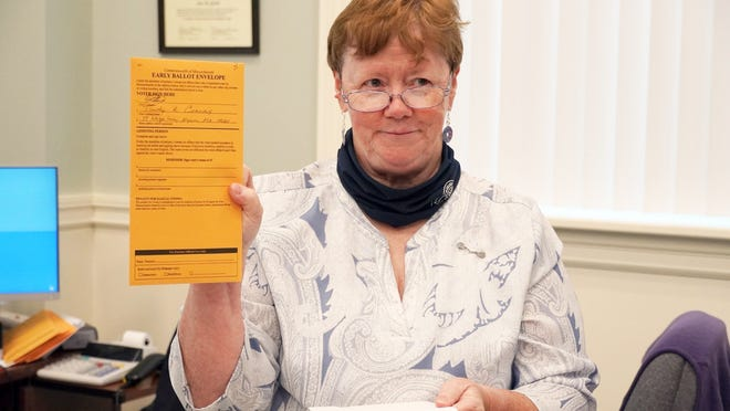 Town Clerk Ann Quirk holds a mail-in ballot, one of 13,196 requests her staff has received to date.