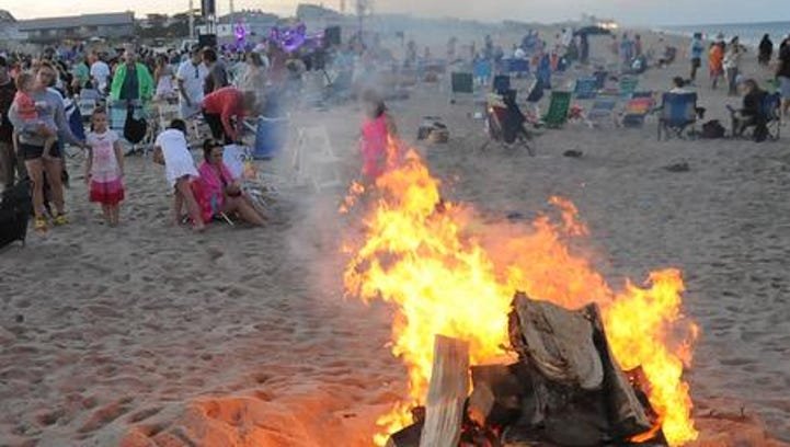 The bonfire glows as the sun begins to set.