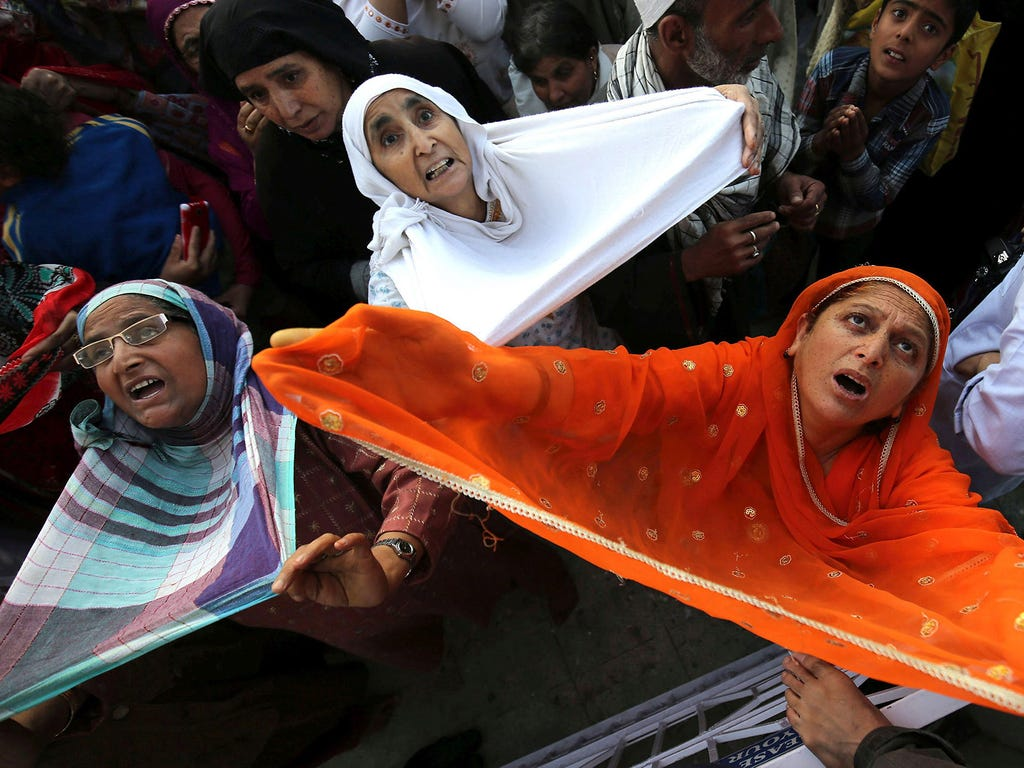 Muslim women pray as a priest displays a holy relic believed to be the hair from the beard of the prophet Muhammad, on May 22 at the Hazratbal Shrine outside Srinagar, India.