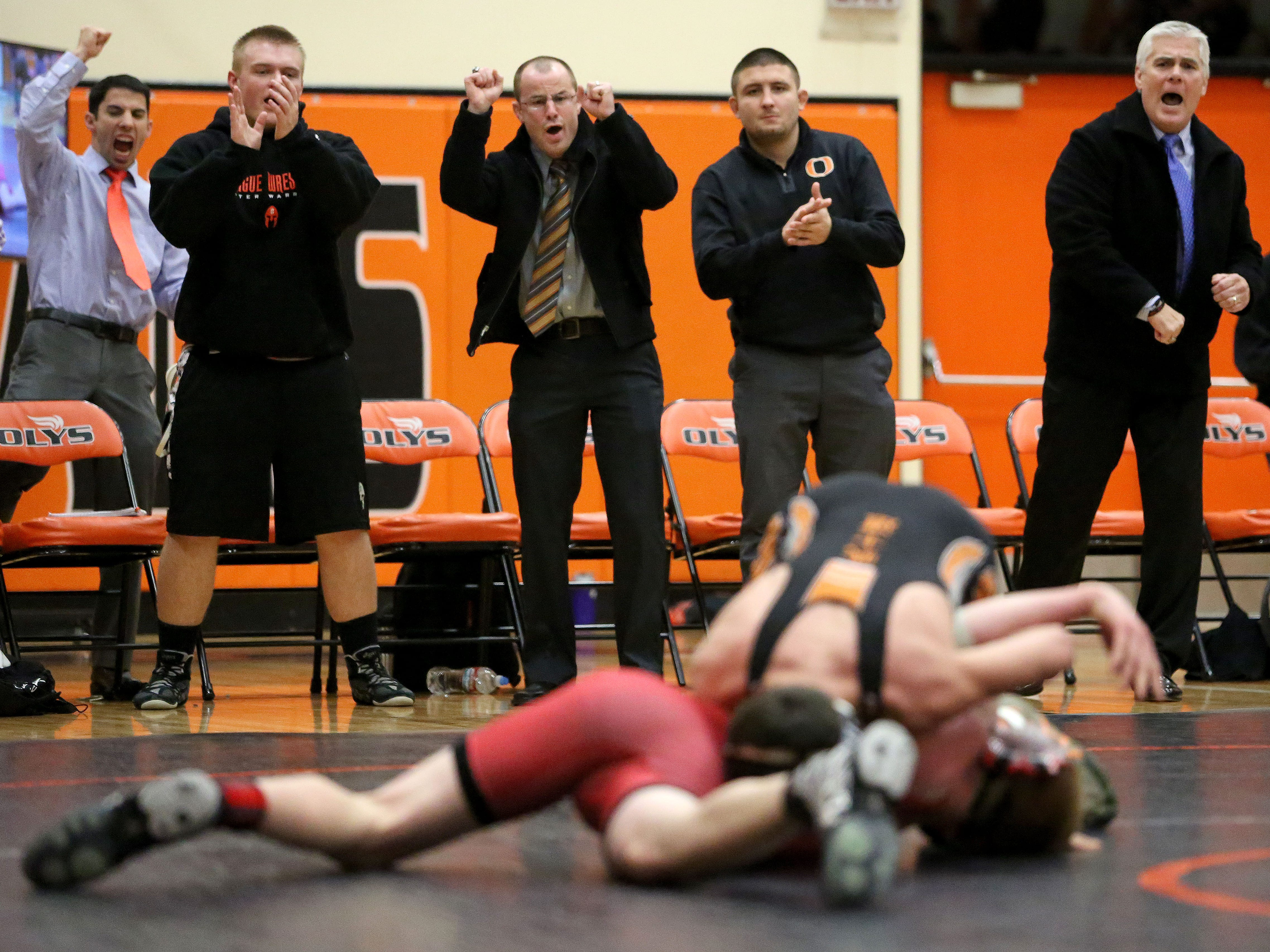 Sprague High School wrestling team's bench cheers for Jared Hampl during his match with McMinnville's Chance Atkinson.