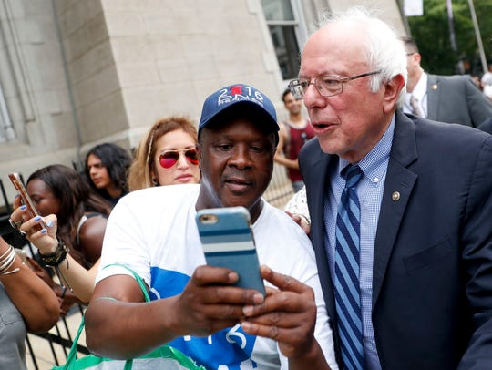 Sen. Bernie Sanders, I-Vt., right, takes a selfie with