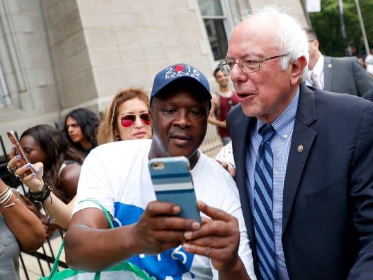 Sen. Bernie Sanders, I-Vt., right, takes a selfie with