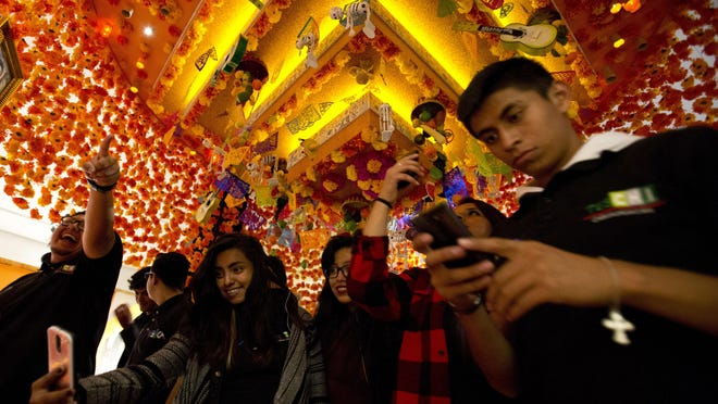 "Students take pictures under a Day of the Dead altar hanging from the ceiling as they visit an exhibition featuring art from the Disney-Pixar animated film ""Coco,"" at the Cineteca Nacional, Mexico's film archive, in Mexico City, Thursday, Nov. 16, 2017. The Day of the Dead themed movie has won over the Mexican public and critics, who praised its mix of tradition, a family-friendly story, and a moving message. (AP Photo/Rebecca Blackwell)"
